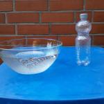 Schüssel mit Wasser, leere Plastikflasche mit Löchern im Boden