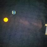 Experiment 14, Bild 2: Wie entstehen die Mondphasen? Auge und beide Bälle müssen eine Linie bilden. Die nahe Kugel stellt die Erde da, die entfernte den Mond.