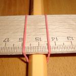 Experiment 25, Bild 2: Das Lineal mit dem Gummiband am Bleistift/Buntstift befestigen