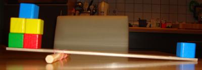 Experiment 25, Bild 8: Jetzt umgekehrt. Verschiebt man den Drehpunkt nach links, braucht es nur noch sehr wenig Kraft, um große Lasten zu heben. Ein fünftel der Last ist ausreichend als Gegengewicht.