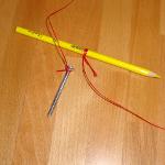 Experiment 27, Bild 2: Den Breitengrad bestimmen mit Winkelmesser, Schnur, Bleistift, Tesafilm, Schraube und Polarstern. Die Schnur am Bleistift und der Schraube befestigen.