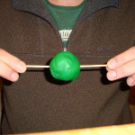 Experiment 29, Bild 3: Wie entstehen Tag und Nacht, Kugel vor die Brust halten, Heftzwecke zum Bauch
